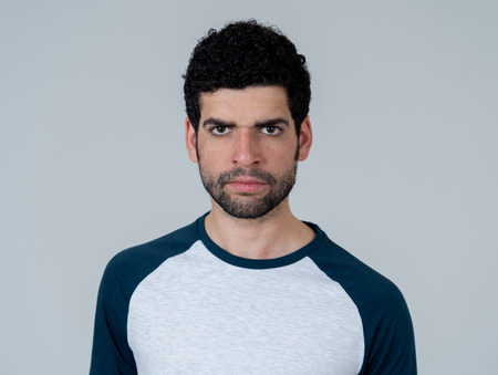 Portrait of young hipster male looking furious with angry displeased and annoyed facial expression. Isolated on neutral background. In people and negative emotions or feelings reaction.