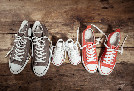 Imagen conceptual de gumshoes zapatillas de deporte de padre, madre e hijo, hija, familia, en, piso de madera, vendimia, en, diferente, tamaños, en, dulce, hogar, unión, familia feliz, crianza, y, estilo de vida, concept.