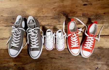Image conceptuelle de chaussures de sport en caoutchouc de la famille père mère et fils fille sur un plancher en bois vintage de différentes tailles dans le concept de convivialité Sweet home Happy Family Parenting et style de vie.