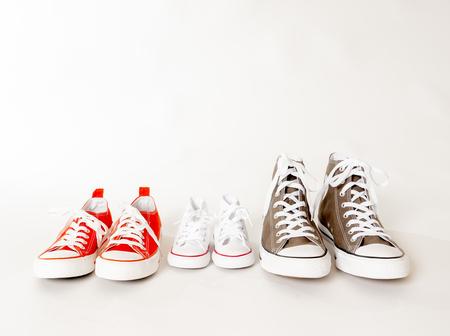 Konzeptionelles Bild von Gummischuhen Turnschuhen von Vater Mutter und Sohn Tochter isoliert auf weißem Hintergrund Kopienraum in verschiedenen Größen in Zusammengehörigkeit Familienerziehung Bildung und Lifestyle-Konzept.