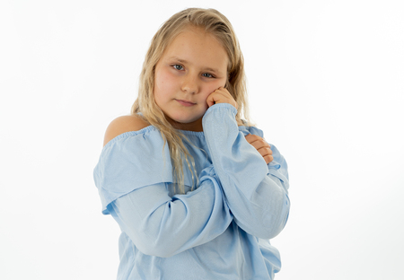 Close up portrait of a cute young shy girl looking timid at the camera on a white background. In facial expression photo concept