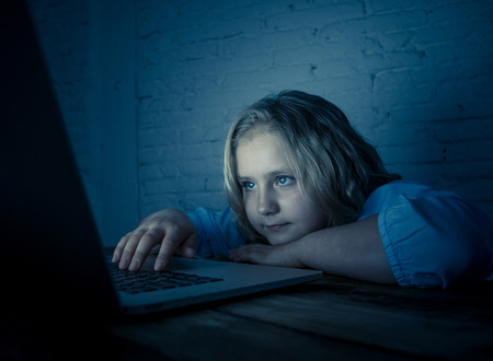 Cute schoolgirl child playing and surfing online late at night. Child addicted to internet games and social media can´t sleep hooked on laptop. Digital technology in childhood and internet addiction.