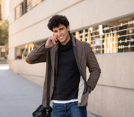 Young attractive man in his twenties happy talking and chatting with friend on social media on smart phone on holidays in europe. In communication, technology internet and lifestyle concept.