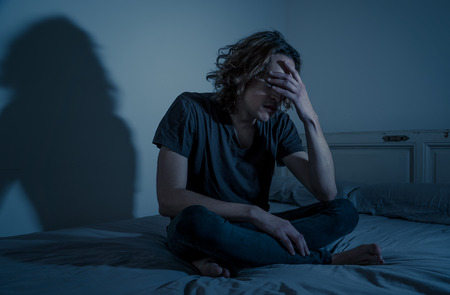 Devastated millennial man crying sad feeling hurt and hopeless suffering Depression. Depressed teenager victim of bullying or abuse sitting on bed alone in despair at night. In teenage Mental health.