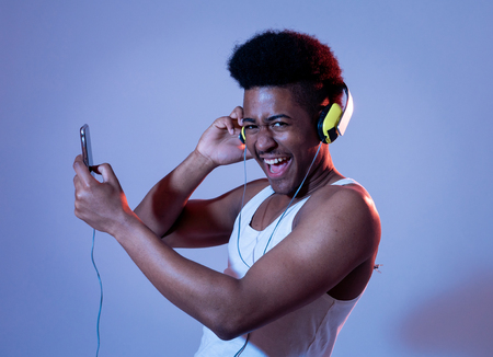 Strong african american young man listening to music in smartphone