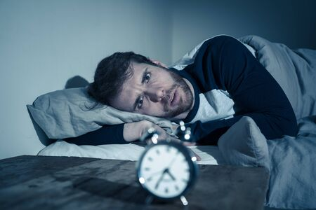 Insomnia Stress and Sleeping disorder concept. Sleepless desperate young caucasian man awake at night not able to sleep, feeling frustrated and worried looking stressed and concerned at alarm clock. Banco de Imagens - 124880774