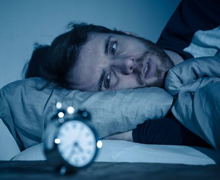 Sleepless and desperate young caucasian man awake at night not able to sleep, feeling frustrated and worried looking at clock suffering from insomnia in stress and sleeping disorder concept. Banco de Imagens - 124880782