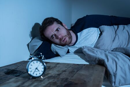 Insomnia Stress and Sleeping disorder concept. Sleepless desperate young caucasian man awake at night not able to sleep, feeling frustrated and worried looking stressed and concerned at alarm clock. Banco de Imagens - 124880788
