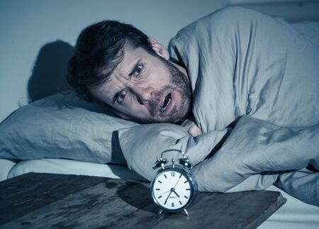 Mental health, Insomnia and sleeping disorders. Frustrated and hopeless sleepless man looking in distress at alarm clock awake at night not able to sleep suffering anxiety caused by stress at work. Stock Photo