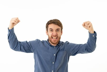 Portrait of young happy and excited man winning the lottery celebrating goal or having great success with fist up cheering. In People success and Facial Expression and positive Human Emotions. Reklamní fotografie