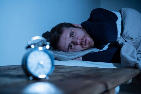 Sleepless and desperate young caucasian man awake at night not able to sleep, feeling frustrated and worried looking at clock suffering from insomnia in stress and sleeping disorder concept. Banco de Imagens - 124880818