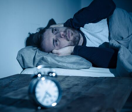 Sleepless and desperate young caucasian man awake at night not able to sleep, feeling frustrated and worried looking at clock suffering from insomnia in stress and sleeping disorder concept. Фото со стока