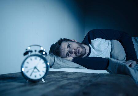 Schlaflosigkeit Stress und Schlafstörungen Konzept. Schlafloser, verzweifelter junger Kaukasier, der nachts nicht schlafen kann, sich frustriert und besorgt fühlt und gestresst und besorgt auf den Wecker schaut