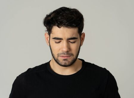 Young sad man suffering from depression looking serious and concerned. Teenager worried and thoughtful feeling lonely and hopeless Isolated on neutral background.People and mental health care. Reklamní fotografie