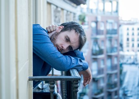 Lonely sad man staring outside house balcony feeling depressed distress and miserable. Suffering emotional crisis thinking about difficult important life decision In Men Depression and mental health. 写真素材