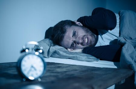Sleepless and desperate young caucasian man awake at night not able to sleep, feeling frustrated and worried looking at clock suffering from insomnia in stress and sleeping disorder concept. Banco de Imagens - 124885344