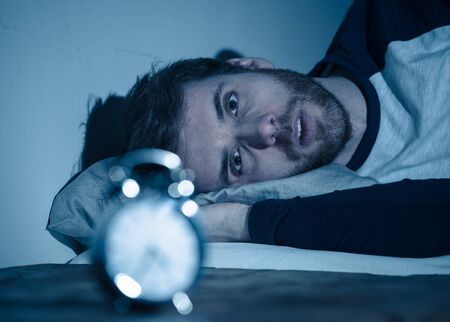 Insomnia Stress and Sleeping disorder concept. Sleepless desperate young caucasian man awake at night not able to sleep, feeling frustrated and worried looking stressed and concerned at alarm clock. Banco de Imagens - 124885345