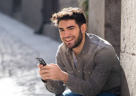 Fashion college man in his twenties happy checking blog or chatting on the internet with friends on smart mobile phone app in european outdoors city. In communication technology and travel Europe.