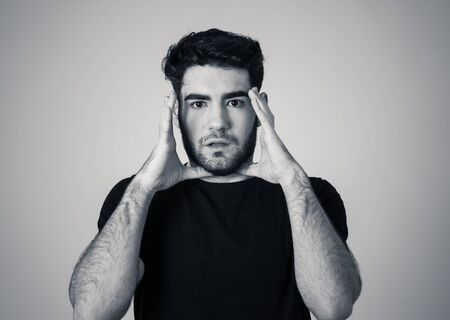 Young man feeling scared and shocked making fear anxiety gestures. Looking terrified and desperate trying to cover himself. Portrait with copy space. People and Human expressions and emotions.