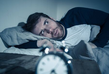 Insomnia Stress and Sleeping disorder concept. Sleepless desperate young caucasian man awake at night not able to sleep, feeling frustrated and worried looking stressed and concerned at alarm clock. Banco de Imagens - 124932806