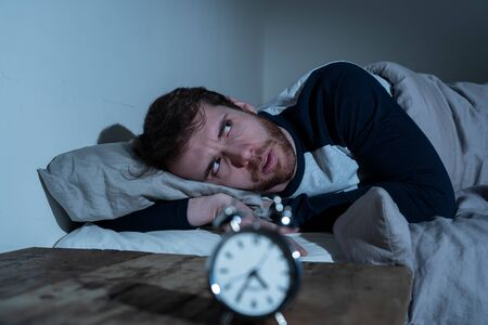 Insomnia Stress and Sleeping disorder concept. Sleepless desperate young caucasian man awake at night not able to sleep, feeling frustrated and worried looking stressed and concerned at alarm clock. Banco de Imagens - 124932846