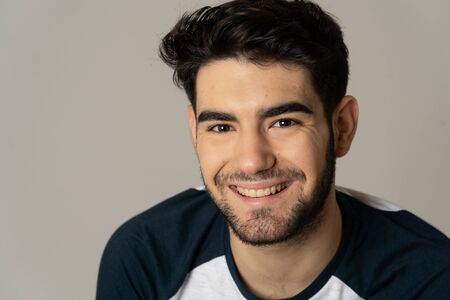 Young attractive stylish fashion man in his 20s looking in casual clothes, unshaven and dark hair posing against neutral background. People and Beauty Portrait of sweet and masculine model.