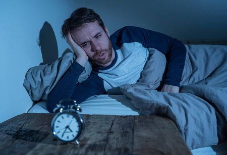 Insomnia Stress and Sleeping disorder concept. Sleepless desperate young caucasian man awake at night not able to sleep, feeling frustrated and worried looking stressed and concerned at alarm clock. Banco de Imagens - 124934106