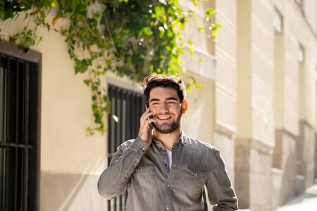 Young happy man in his twenties on mobile phone talking and chatting with friends on social media app on holidays in Europe. In communication, Traveling, technology internet and lifestyle concept.