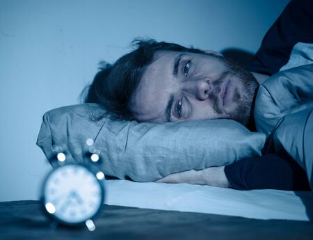 Sleepless and desperate young caucasian man awake at night not able to sleep, feeling frustrated and worried looking at clock suffering from insomnia in stress and sleeping disorder concept. Banco de Imagens - 124934453