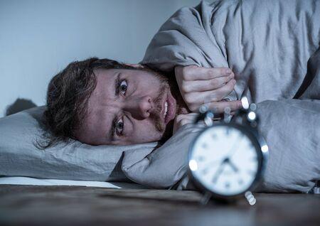 Salud mental, insomnio y trastornos del sueño. Hombre sin dormir frustrado y sin esperanza mirando angustiado en el despertador despierto por la noche sin poder dormir sufriendo ansiedad causada por el estrés en el trabajo.