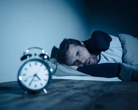 Insomnia Stress and Sleeping disorder concept. Sleepless desperate young caucasian man awake at night not able to sleep, feeling frustrated and worried looking stressed and concerned at alarm clock. Banco de Imagens - 124934462
