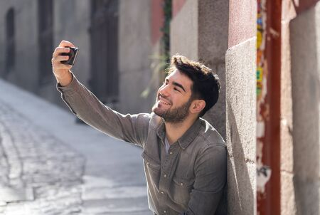 Excited trendy young man taking selfie or blogging on smart mobile phone on holidays in european city street or university campus. Holidays and technology Connection and social media concept.