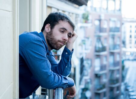 Lonely sad man staring outside house balcony feeling depressed distress and miserable. Suffering emotional crisis thinking about difficult important life decision In Men Depression and mental health. Imagens