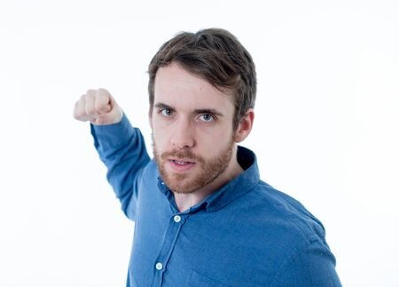Annoyed young bearded man with an angry face looking mad and furious feeling frustrated. Close up studio shot Isolated on white background. People, Facial expressions and negative emotions.