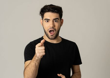 Portrait of a handsome latin young man surprised and shocked hearing great news. Attractive male looking amazed with wide eyes and mouth open in surprise. Human facial expressions and emotions. Imagens
