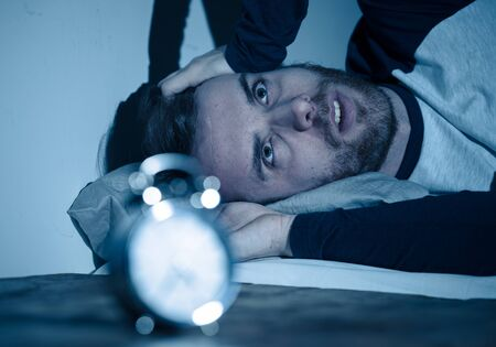 Sleepless and desperate young caucasian man awake at night not able to sleep, feeling frustrated and worried looking at clock suffering from insomnia in stress and sleeping disorder concept. Banco de Imagens - 124934535