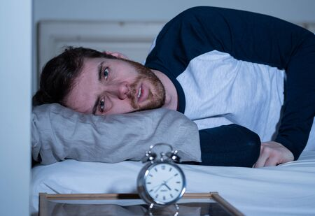 Sleepless and desperate young caucasian man awake at night not able to sleep, feeling frustrated and worried looking at clock suffering from insomnia in stress and sleeping disorder concept. Banco de Imagens - 124934537