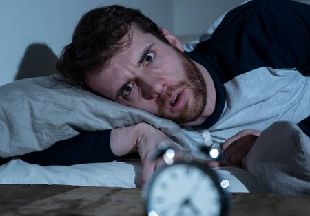 Insomnia Stress and Sleeping disorder concept. Sleepless desperate young caucasian man awake at night not able to sleep, feeling frustrated and worried looking stressed and concerned at alarm clock. Banco de Imagens - 124934553