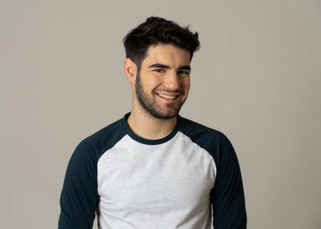 Positive human facial expressions and emotions. Portrait of handsome young male in his 20s with happy face smiling and making cheerful gestures at the camera. Close up Isolated on neutral background.