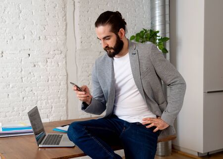 Happy successful entrepreneur checking mobile phone while working in modern cool home office. Lifestyle portrait of freelancer owner of small company In successful people and business concept.