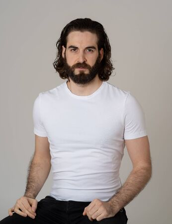 Portrait of Attractive stylish fashion man in his 20s looking sexy with beard, long dark hair and brown eyes. Masculine hipster model posing against neutral background. In People and Beauty concept.