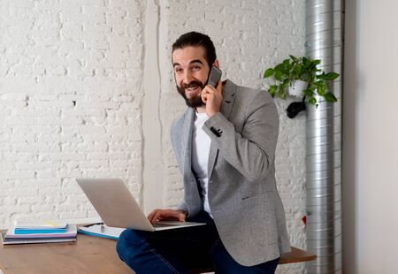 Portrait of hipster successful business owner talking business on mobile smartphone while working on laptop in modern studio office. In People startup small Business Communication and technology.