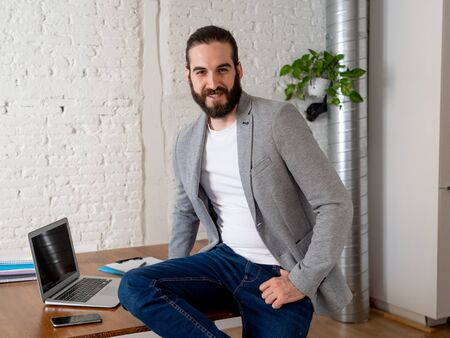 Portrait of confident young executive entrepreneur in modern home office working space. Young Hipster small business owner posing for the camera In People startup Self employee and business success.
