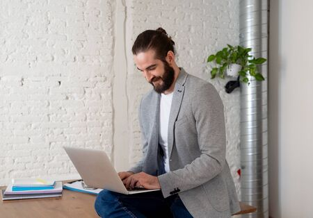 Successful hipster entrepreneur working on laptop in his modern studio home office. Looking happy and confident with own business success. In People startup and successful young businessmen concept. Stock Photo