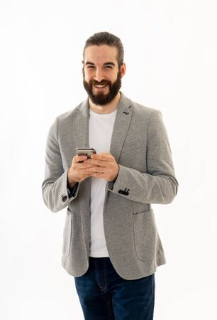 Portrait of handsome successful hipster emailing and sending messages on mobile smartphone or on social media network isolated on white background. In People Internet Communication and technology. 写真素材