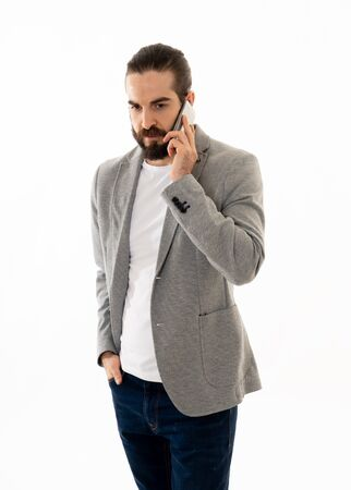Portrait of young Hipster entrepreneur talking business on mobile smartphone feeling confident and successful. In people, freelance business communication and technology concept. Banco de Imagens - 124973205