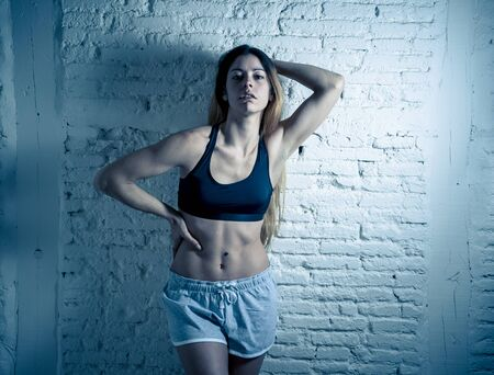 Attractive fitness woman wearing gym top and pants looking sensual and fit. Studio shot of strong woman in sportswear looking healthy against brick wall. In female trained Body and health care.
