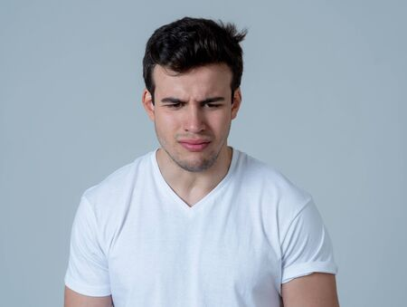 Portrait of a young sad latin man depressed and hopeless crying in emotional pain. Feeling sorrow and suicidal Isolated in neutral background. In People human emotions and mental health concept.