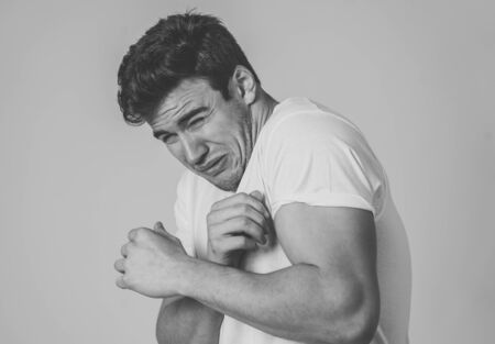 Portrait of Handsome latin young man in shock with a scared expression on his face making frightened and defence gestures in human emotions feelings and facial expression. Studio shot.
