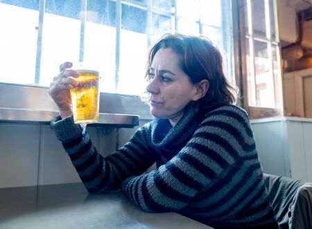 Portrait of a attractive latin woman drinking beer in a bar pub feeling depressed unhappy and lonely in Alcohol Use Abuse Depression and mental health concept. Stock Photo